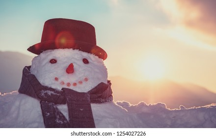 Portrait of a snowman dressed in hat and scarf over sunset background, fun wintertime tradition, happy winter holidays
