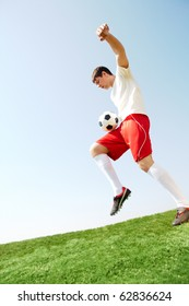 Portrait of soccer player with ball over leg playing on football field