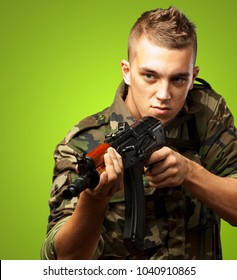Portrait Of A Soldier Aiming With Gun against a green background