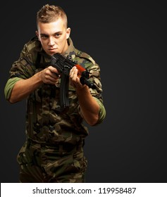 Portrait Of A Soldier Aiming With Gun against a black background
