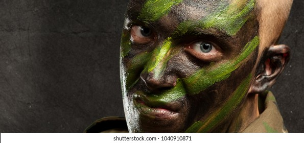 portrait of a soldier with camouflage painting against a grunge background