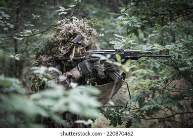 portrait of the soldier dressed in ghille suit, aiming with  assault rifle in forest. rifle painted camouflage.