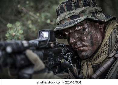portrait of soldier dressed in tiger stripe camouflage with assault rifle