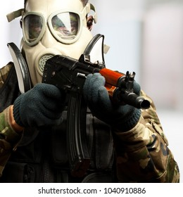 Portrait Of A Soldier With Gas Mask Aiming With Gun against an abstract background