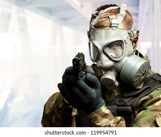 Portrait Of A Soldier With Gas Mask Aiming With Gun, indoor
