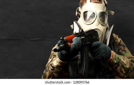 Portrait Of A Soldier With Gas Mask Aiming With Gun against a grunge background