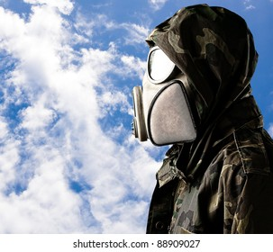 portrait of soldier with gas mask and hood against a cloudy sky background