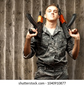 Portrait Of Soldier Holding Gun On a wooden Background
