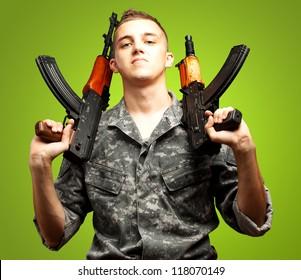 Portrait Of Soldier Holding Gun On green Background