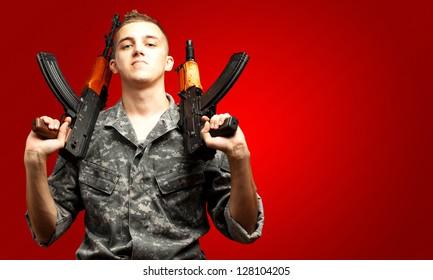 Portrait Of Soldier Holding Gun On red Background
