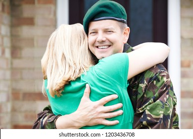 Portrait Of Soldier Hugging Wife Home On Leave From Army