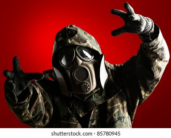 portrait of soldier with jungle camouflage and gas mask trying to hold something over red