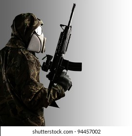 portrait of soldier with mask and rifle against a grey background
