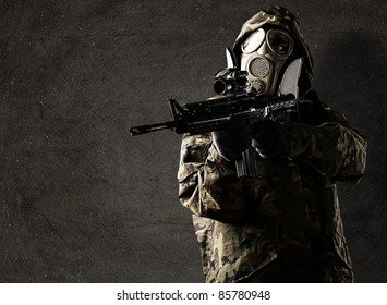 portrait of soldier with rifle and gas mask against a grunge background