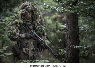 portrait of the soldier wearing ghille suit, holding assault rifle in forest.