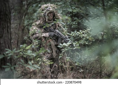 portrait of the soldier wearing ghille suit, holding assault rifle in deep forest. rifle painted camouflage. face painted camouflage.