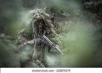 portrait of the soldier wearing ghille suit, hidden in forest