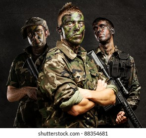 portrait of soldiers group with jungle camouflage against a grunge wall