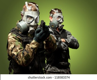 Portrait Of Soldiers With Gun And Gas Mask Against Green Background
