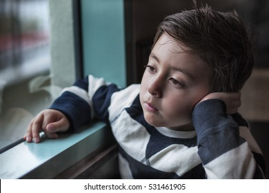 Portrait of a somber little boy in blue and white stripped sweater staring outside through a window on a dark winter morning