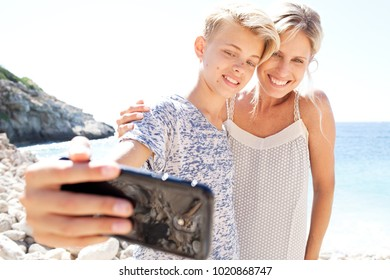 Portrait of son and mother posing taking selfie photo with smart phone on holiday, flare sunny sky outdoors. Family day out using technology, travel leisure recreation lifestyle, heads together.