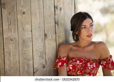 Portrait southern Italian woman smile and long straight brown hair posing elegantly while looking out of the picture with red flowered dress leaning against vertical slatted wooden wall