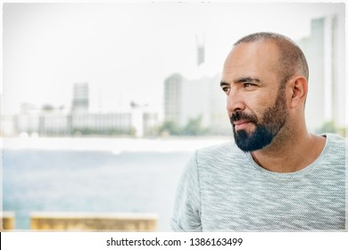 Portrait of a spanish man with beard and short buzz hair, looking away, casual, pensive, dreaming, profile view over urban background.