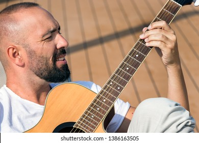 Portrait of a spanish man with beard and short buzz hair, playing an acoustic guitar outdoors.