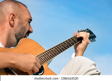 Portrait of a spanish man with beard and short buzz hair, playing an acoustic guitar outdoors over a blue sky background.