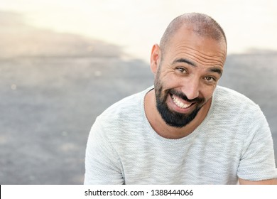 Portrait of a spanish man with beard and ultra short buzz, smiling in a funny way, looking camera, wearing a t-shirt, outdoors.