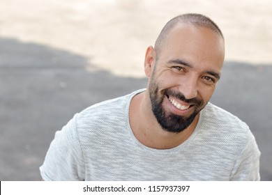 Portrait of a spanish man with a beard and very short buzz hair cut, smiling looking camera, happy toothy smile, outdoors.