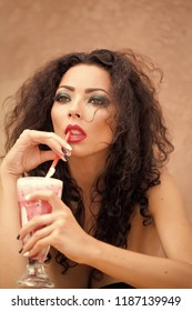 Portrait of splendid charming brunette girl with fashion makeup long curly hair looking away thoughtful holding glass of cocktail with red straw on light background, vertical picture