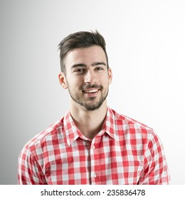 Portrait of spontaneous smiling positive young bearded man over gray background.