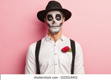 Portrait of spooky handsome guy made makeup for Halloween event, has image of vampire or ghost, red rose flower in pocket of white shirt, wears black hat, has scary look, dressed in zombie attire