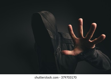 Portrait of spooky hooded unrecognizable person without face in dark room