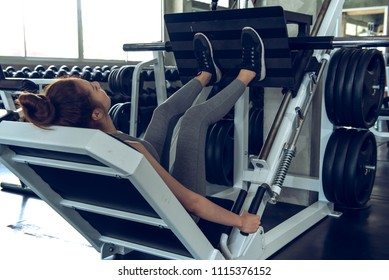 Portrait sport girl doing leg presses in the gym with smiling face, fitness and exercise concept.