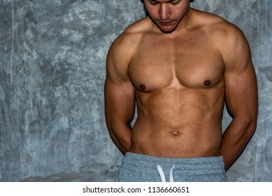 Portrait of sport male model showing his muscle with loft cement wall background.