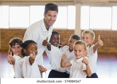 Portrait of sport teacher and students showing thumbs up in school gym