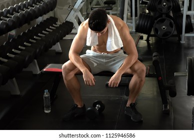 Portrait of sport young fitness man with white towel on his neck, relax after exercise at indoor sport gym, healthy sport concept.
