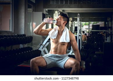 Portrait of sport young fitness man with white towel on his neck, drinking water, relax after exercise at indoor sport gym, healthy sport concept.