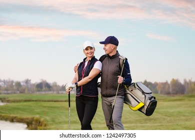 Portrait of sportive couple golfers playing golf at autumn day