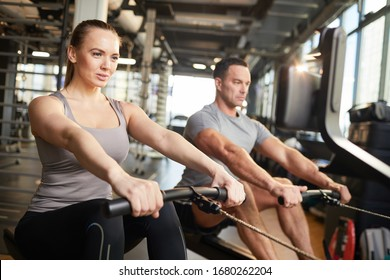 Portrait of sportive couple using exercise machines during strength workout in modern gym, copy space