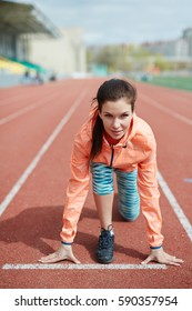Portrait of sportive woman ready to start running on stadiums sprint track