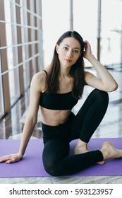 Portrait of the sports and beautiful girl in the gym at windows.