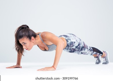 Portrait of a sports woman doing push ups isolated on a white background