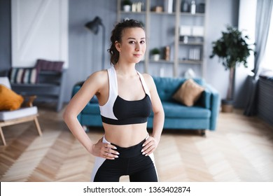 Portrait of a sports woman in the living room at home. Sport and lifestyle concept.