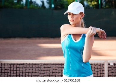 Portrait of a sports woman stretching hands outdoors. in court