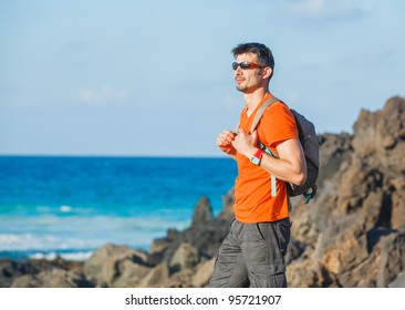 Portrait of a sports young man with backpack. in the background of the sea