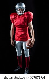 Portrait of sportsman with American football standing against black background