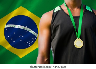 Portrait of sportsman chest with a medal against digitally generated brazilian national flag